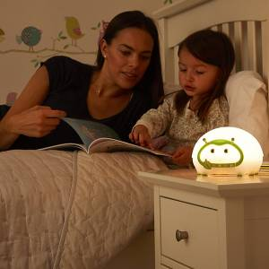 Mother reading to daughter in bed with the Lumie bedbug turned on