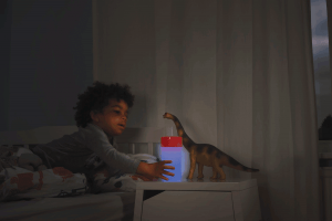 Child reaching for his litecup to have a drink of water at night