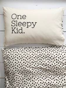 Both sides of the 'one sleepy kid' pillow covers, where one side has the leaf print to match the duvet cover and the other side has text 'one sleepy kid' printed