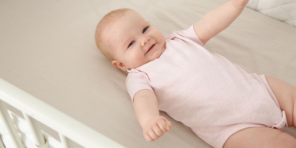 Smiling baby in a cot