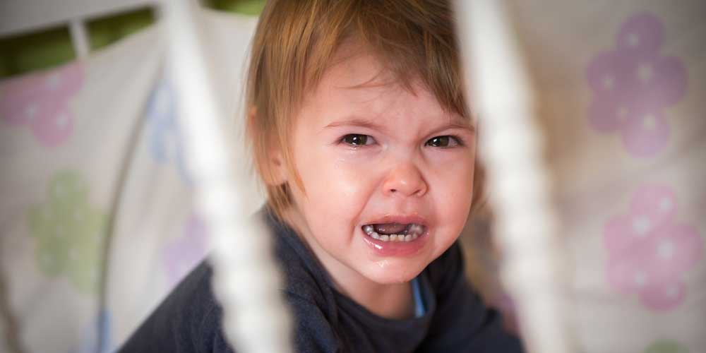 Toddler crying in a cot